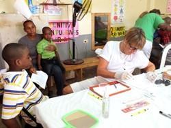 Dentista voluntaria realizando su trabajo para mejorar la salud dental de los niños en Jamaica.