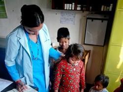 Enfermera profesional voluntaria tratando a unos niños en Nepal