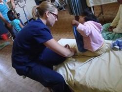 Fisioterapeuta profesional voluntaria asistiendo a una paciente en Bolivia.