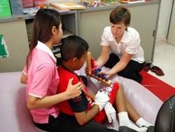 Fisioterapeuta voluntaria realiza con un niño una actividad terapeútica en una clínica de Camboya