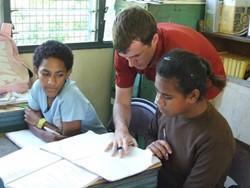 Voluntario profesional realizando ejercicios de lenguaje con niños en Fiyi