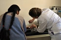 Médico voluntario atiende a un paciente y a su madre en uno de los proyectos de voluntariado en Bolivia