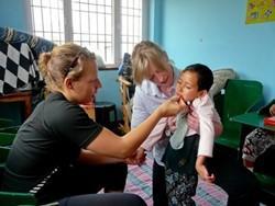 Médico voluntario trabaja con niños en un proyecto en Nepal