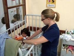Terapeuta ocupacional voluntaria trata a un bebé en una clínica en Bolivia