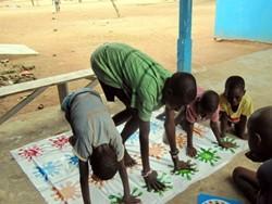 Voluntarios en el proyecto de terapia ocupacional en Ghana enseñan a unos niños juegos de coordinación