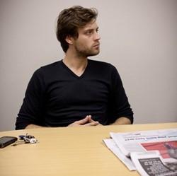 Periodista voluntario sentado en una reunión de la plantilla