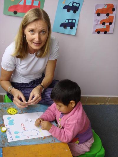 Trabajadora Social voluntaria ayudando a niño en actividad en Bolivia