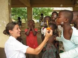 Trabajador social voluntario hace pompas de jabón con un niño en un centro social.