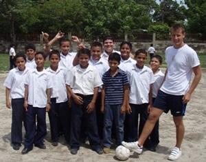 Un voluntario del Proyecto de Deportes Escolares en Costa Rica junto a un grupo de niños locales en un recreo en las prácticas de fútbol