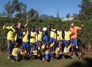 Los jóvenes miembros del equipo de fútbol de la escuela posan para una foto con los voluntarios de Projects Abroad.