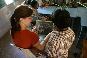 Una voluntaria de Projects Abroad en el Proyecto de Enseñanza ayuda con las tareas de matemáticas a un niño pequeño en una escuela en Bangladés