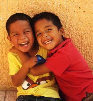 Niños abrazados y sonriendo en Proyecto de Enseñanza en Belice