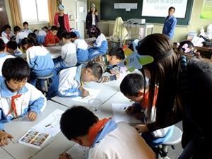 Una voluntaria de Projects Abroad enseña a niños acerca de los tiburones en una escuela de China.