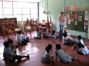 Una voluntaria de Projects Abroad enseña los colores a sus alumnos, mientras que ellos, sentados en un círculo, escuchan atentos.