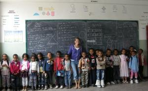 Volunteer with a group of children in a classroom