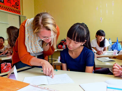 Voluntaria ayudando a estudiante en Mongolia