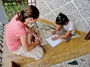 : Una voluntaria de Projects Abroad acompaña a una niña de Nepal mientras dibuja en el Proyecto de Enseñanza