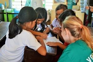 Voluntaria de Projects Abroad ayuda con la tarea a niñas en una escuela primaria en Filipinas