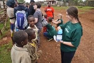 Voluntaria americana de un proyecto de medicina da pastillas para los parásitos a niños locales de Nanyuki