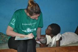 Un estudiante en prácticas en trabajo social de Projects Abroad habla con niño ghanés en Ghana, África.